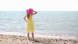 Young woman in hat looking at the sea
