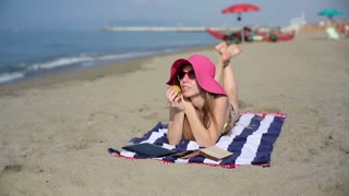Young woman in hat relaxing on beach and eating apple
