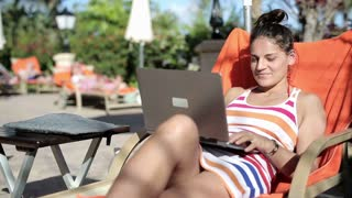 Young woman lying on sunbed and closing laptop computer