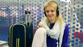 Young woman sitting at the station and listening music