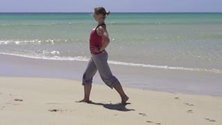 Young woman stretching on the beach, slow motion shot at 240fps