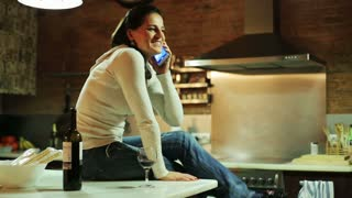 Young woman talking on cellphone and drinking wine in her kitchen