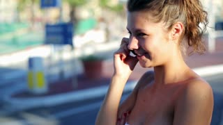Young woman talking on cellphone on the street, steadycam shot