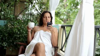 Young woman with cellphone drinking coffee in the morning, outdoors
