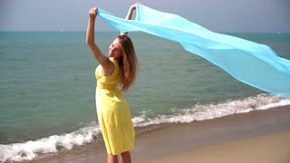 Young woman with waving sarong at the beach, slow motion