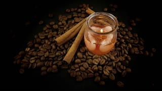 Aromatic Candle & Cinnamon Sticks on Coffee Beans