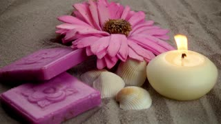 Candle,pink flower and Soaps on the Sand