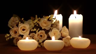 Candles and flowers on black background
