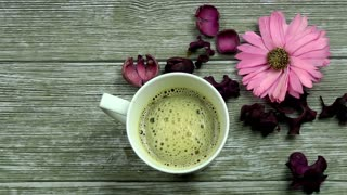 Cup of coffee with flowers on wooden background