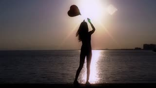 Girl with heart balloon at seaside