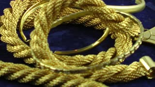 Gold jewellery rotating on dark blue background