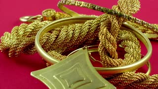 Gold jewellery rotating on red background