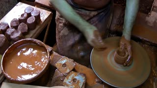 Hands of a man potter creating an earthen jar on the circle from soft clay