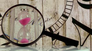 Hourglass and wooden clock and magnify glass