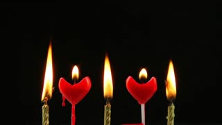 Melting red heart candles and gold candles