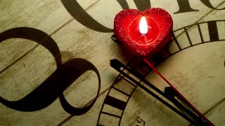 Red heart candle that stops the seconds on wooden clock
