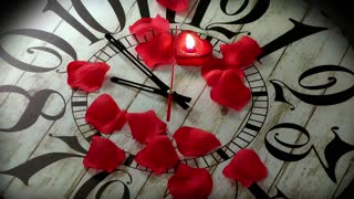Red rose petals and a red heart candle that stops the seconds on wooden clock