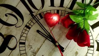 Red roses and a red heart candle that stops the seconds on wooden clock