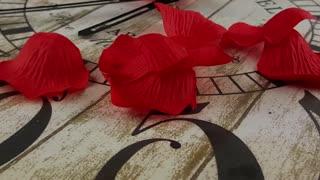 Rose petals on wooden clock