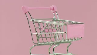 Shopping cart on pink background