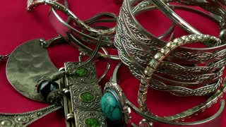Silver jewellery rotating on red background