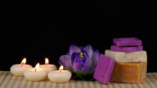 Spa concept with candles,soaps and waterlily on wooden background