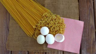 Pasta and eggs on wooden background