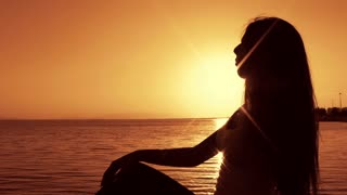 Woman silhouette- Young Woman Relaxing at Sunset