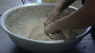 Baker kneads the dough by hands