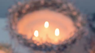 Candles in vase with snow and spruce needles