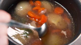 Chef cooks vegetable broth with carrot, onion and spices, slow motion cooking