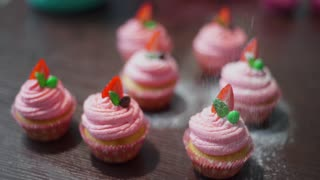 Chef decorates cupcakes with the sugar powder, housewife bakes, cooking in the kitchen, deliciuos and beautiful food
