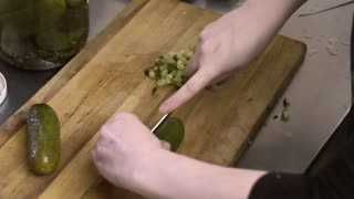 Cook cuts the canned cucumbers on the wooden board by knife in the kitchen