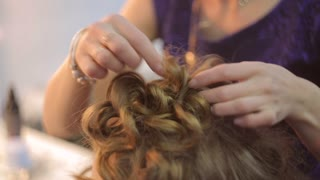 Female barber makes hairstyle for model
