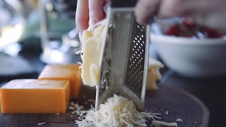 Female chef grates the cheese on a grater in slow motion