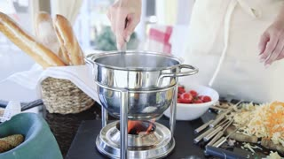 Female chef stirs fondue over low heat