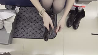 Female trying on a pair of high leather boots in a shoe store