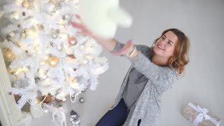 Girl is happy because of unpacking christmas gifts, presents under the tree, celebration of winter holidays, winter decorations