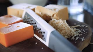 Grater and pieces of cheese on the wooden board