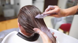 Hairdresser does hair coloring in beauty studio, woman changes her look, professional coloring and hair care, beauty business
