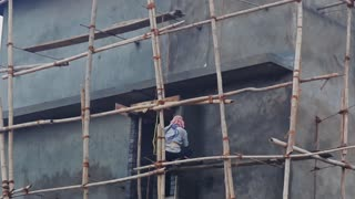Indian construction worker works at high altitude