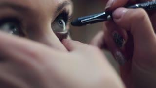 Make-up artist makes eye liner for client