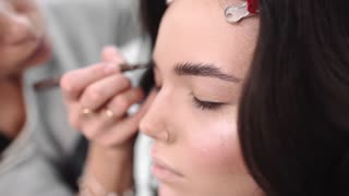 Make up artist paints eyebrows by pencil, Make up artist does make up for model, woman in beauty salon, photo model gets ready for photoshoot