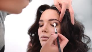 Make up stylist makes smokey eyes effect for woman at photo shoot, make up for beautiful caucasian model, girl comes to beauty fashion salon