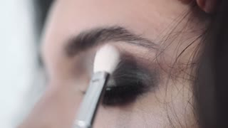 Make up stylist makes smokey eyes effect for woman at photo shoot, make up for beautiful caucasian model, girl comes to beauty salon