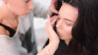 Makeup artist applies the tone to the skin, visagist makes make up for beautiful caucasian woman, white girl with pretty face at the beauty salon