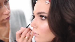 Makeup artist draws arrows, visage master makes eye make up, woman come to beauty salon, woman ask make up artist to do smokey eyes