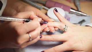 Manicurist paints woman's nails by brush, woman comes to the manicure salon, nail care, business in beauty
