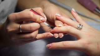 Master of manicure covers woman's nails by transparent nail polish, woman comes to the manicure salon, nail care, business in beauty