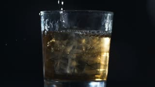 Alcohol is poured to the glass with ice cubes in slow motion, barman makes drinks, 240 frames per second